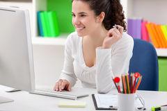 Cheerful young woman using computer Royalty Free Stock Image