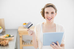 Cheerful young woman using her tablet for home shopping sitting in her kitchen Stock Image