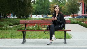 Cheerful young woman using mobile phone on a bench in a park, young woman smiling while browsing internet stock video footage
