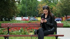 Cheerful young woman using mobile phone on a bench in a park, young woman smiling while browsing internet stock video