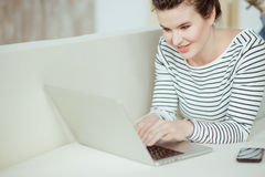 Cheerful young woman is using a notebook Royalty Free Stock Photo