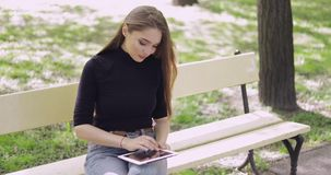 Cheerful young woman using tablet outside stock video footage