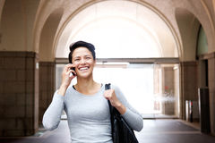 Cheerful young woman walking with cell phone and bag Royalty Free Stock Photos