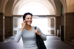 Cheerful young woman walking with mobile phone and bag Stock Photo
