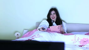 Cheerful young woman watching television Stock Images