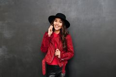 Cheerful young woman wearing hat talking by mobile phone. Photo of cheerful young woman wearing hat standing over dark grey wall chalkboard talking by mobile Stock Photos