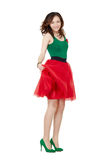 Cheerful young woman wearing red skirt. Studio body portrait of cheerful young woman wearing a tulle red skirt and high heels royalty free stock photos