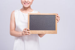 Cheerful young woman in white singlet holding sign over gray bac Stock Photos