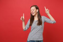 Cheerful young woman with wireless earphones dancing, pointing index fingers up, listening music isolated on bright red. Wall background. People sincere stock photo