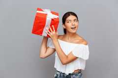 Cheerful young woman wonder what is inside present box Stock Photography