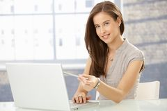 Cheerful young woman at work Stock Images