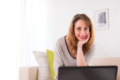 Cheerful young woman working at home with laptop Royalty Free Stock Photo