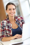 Cheerful young woman working on laptop Royalty Free Stock Photos