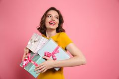 Cheerful young woman in yellow dress holding heap of presents Royalty Free Stock Images
