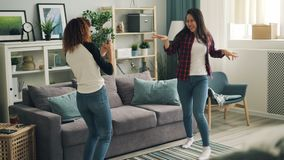 Cheerful young women are dancing at home relaxing and listening to music while African American girl is recording video stock video