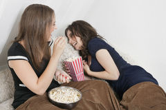 Cheerful young women eating popcorn in bed Stock Photos