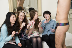 Cheerful young women enjoying while male stripper performing Royalty Free Stock Photography