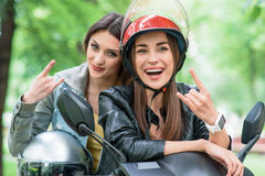 Cheerful young women gesturing on bike. Joyful female friends are traveling by scooter in park. Girls are showing rock-and-roll sign and laughing Royalty Free Stock Images