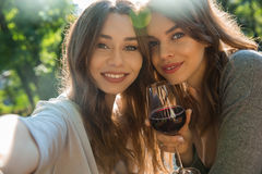 Cheerful young women outdoors in park drinking wine make selfie royalty free stock photography
