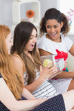 Cheerful young women surprising friend with a gift Royalty Free Stock Photos