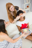 Cheerful young women surprising friend with a gift Stock Image
