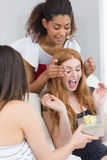 Cheerful young women surprising friend with a gift Royalty Free Stock Image