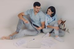 Cheerful young woman uses banking app on her mobile phone, his husband shows figures on calculator, surrounded with papers, have royalty free stock images
