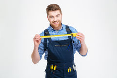 Cheerful young worker in overall smiling and holding measuring tape. Cheerful attractive young worker in overall smiling and holding measuring tape Royalty Free Stock Photo
