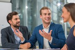 Cheerful young working team in conference hall Royalty Free Stock Images