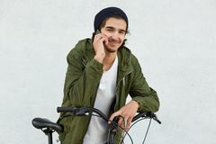 Cheerful youngster with little beard, has pleasant talk with girlfriend via smart phone, wears fashionable hat and anorak, leans a. T his bicycle, has pleased stock images