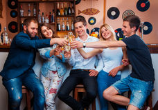 Cheerful youth company is celebrating with champagne at bar Stock Photography