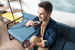Cheerful youthful guy enjoying his hot beverage at home Stock Photos