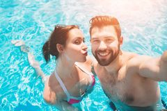 Cheerful youthful guy and lady resting while swimming pool outdoor. Couple in water. Guys do summer sephi.  Stock Photos
