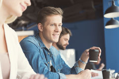 Cheerful youthful guy and other employees doing job in office Royalty Free Stock Image