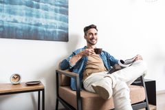 Cheerful youthful man taking pleasure from hot beverage at home Stock Photos