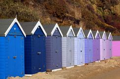 Cheerfull beach huts. A row of huts by a sandy beach, painted in a range of colours from blue through to pink Stock Photo