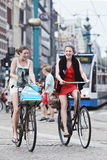 Cheerfull cycling girls in Amsterdam. AMSTERDAM-AUG. 19, 2012. Cheerfull cyclists on Aug. 19 in Amsterdam. 38% of traffic movement in the city is by bike , 37% Royalty Free Stock Images