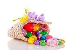 Cheerfull easter eggs. Colorful easter eggs in a wicker shopping basket decorated with krokus flowers isolated Royalty Free Stock Images