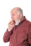 Cheerfull hög man som äter äpplet som isoleras på vit Royaltyfria Bilder