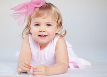 Cheerfull little girl. A cheerfull three year old girl with big pink pow plaing with pearl necklace Royalty Free Stock Photography