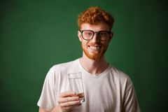 Cheerfull readhead bearded man in glasses, holding glass of wate. R, over green background Stock Photos