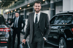 Cheerfull sales manager with booklet at dealership showroom.  Stock Image