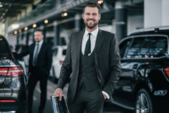 Cheerfull sales manager with booklet at dealership showroom.  Royalty Free Stock Image