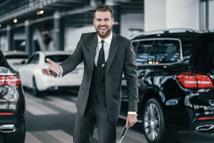 Cheerfull sales manager with new car keys at dealership showroom.  Stock Photo