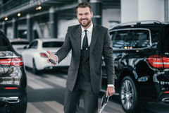 Cheerfull sales manager with new car keys at dealership showroom.  Stock Images