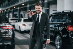 Cheerfull sales manager with new car keys at dealership showroom.  Royalty Free Stock Image