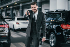 Cheerfull sales manager with new car keys at dealership showroom.  Stock Photos