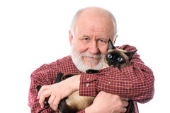 Cheerfull senior man with cat isolated on white. Headshot of cheerful and calm handsome bald and bearded senior man with siamese cat, isolated on white Stock Photos