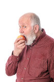 Cheerfull senior man eating the apple, isolated on white Royalty Free Stock Images