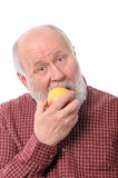 Cheerfull senior man eating the apple, isolated on white Royalty Free Stock Image